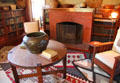 Round arts & crafts table with copper vase before library fireplace at Marston House Museum. San Diego, CA.